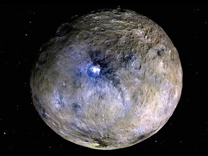 A rocky world covered with craters and bright spots appears brown with splotches of white and purple, the most intense of which is in a large central crater.