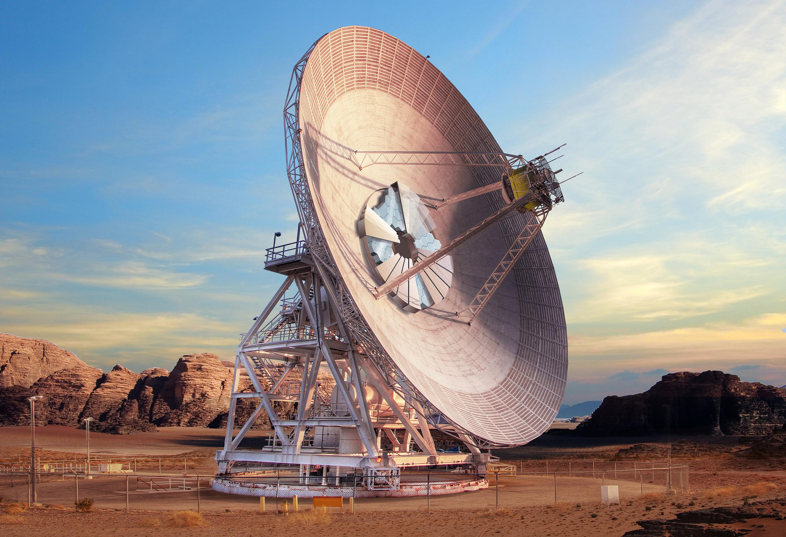 A giant antenna dish is shown in a desert landscape as the sun is setting.