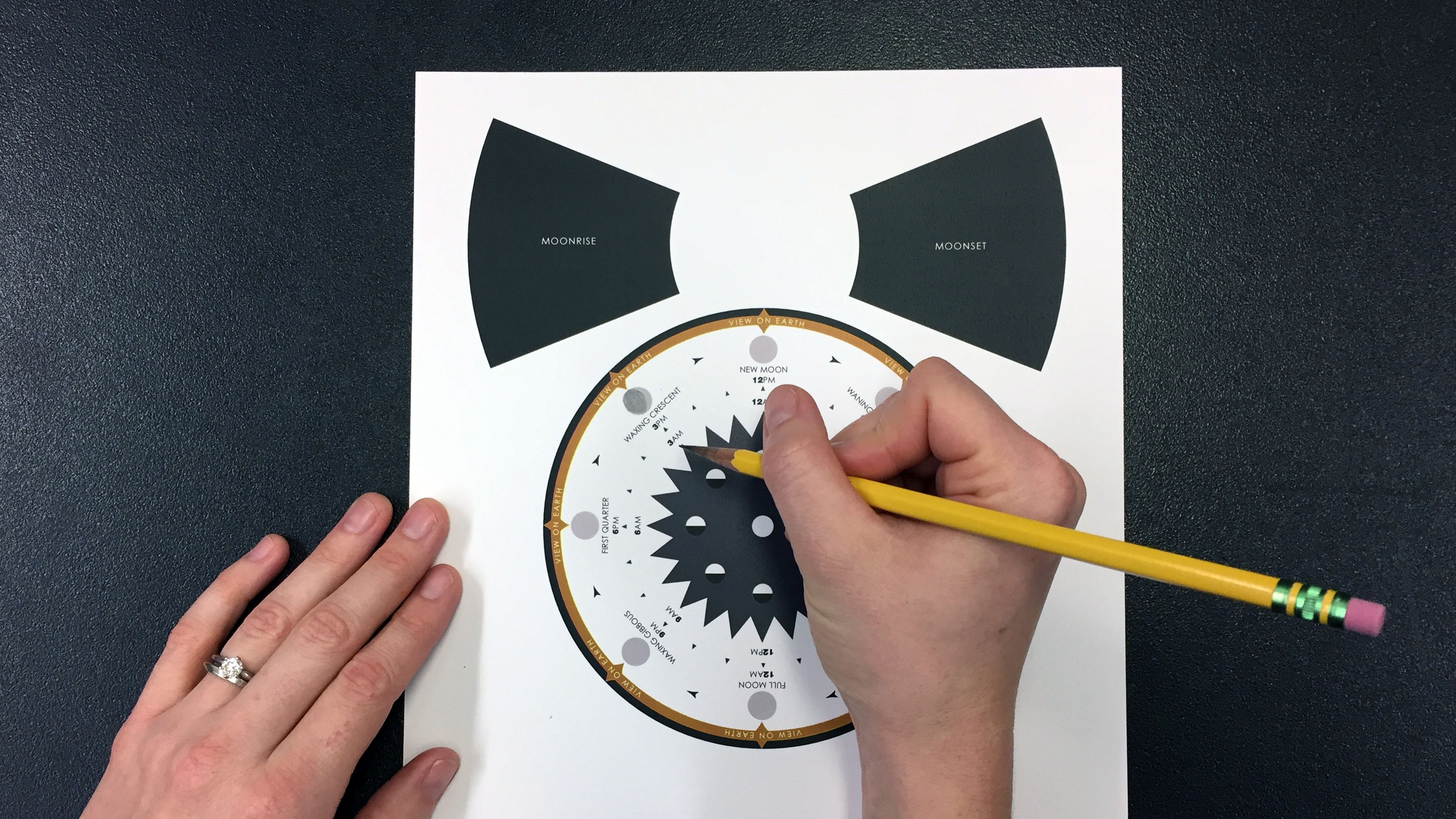A pencil is used to shade in the moon phases on the Moon Phases Wheel