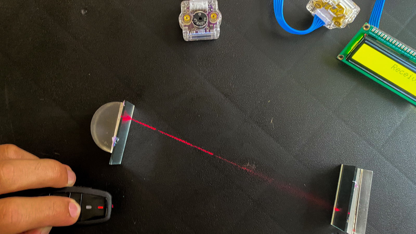 Collage of images showing a red laser pointing at a mirror, the laser hitting a sensor, and a indicator device reading 'receiving'