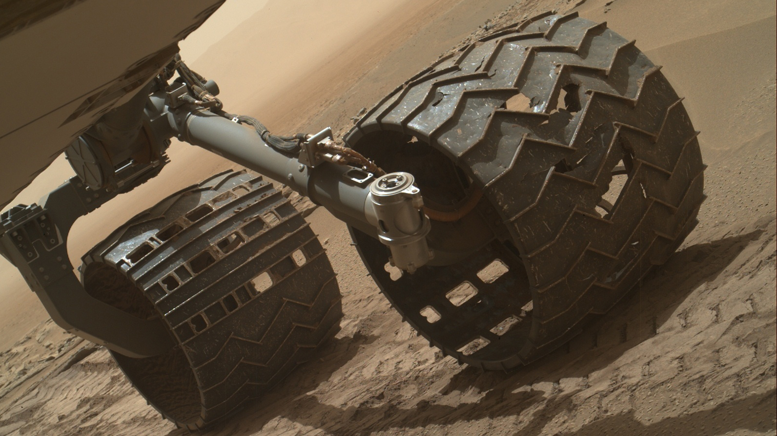 A view of two of the Curiosity rover's wheels that show large holes and damaged sections