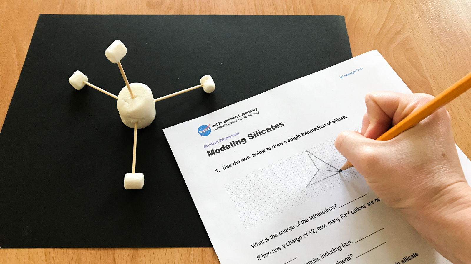 Four mini marshmallows are attached to a large marshmallow in the form of a tetrahedral next to a drawing of a tetrahedral.