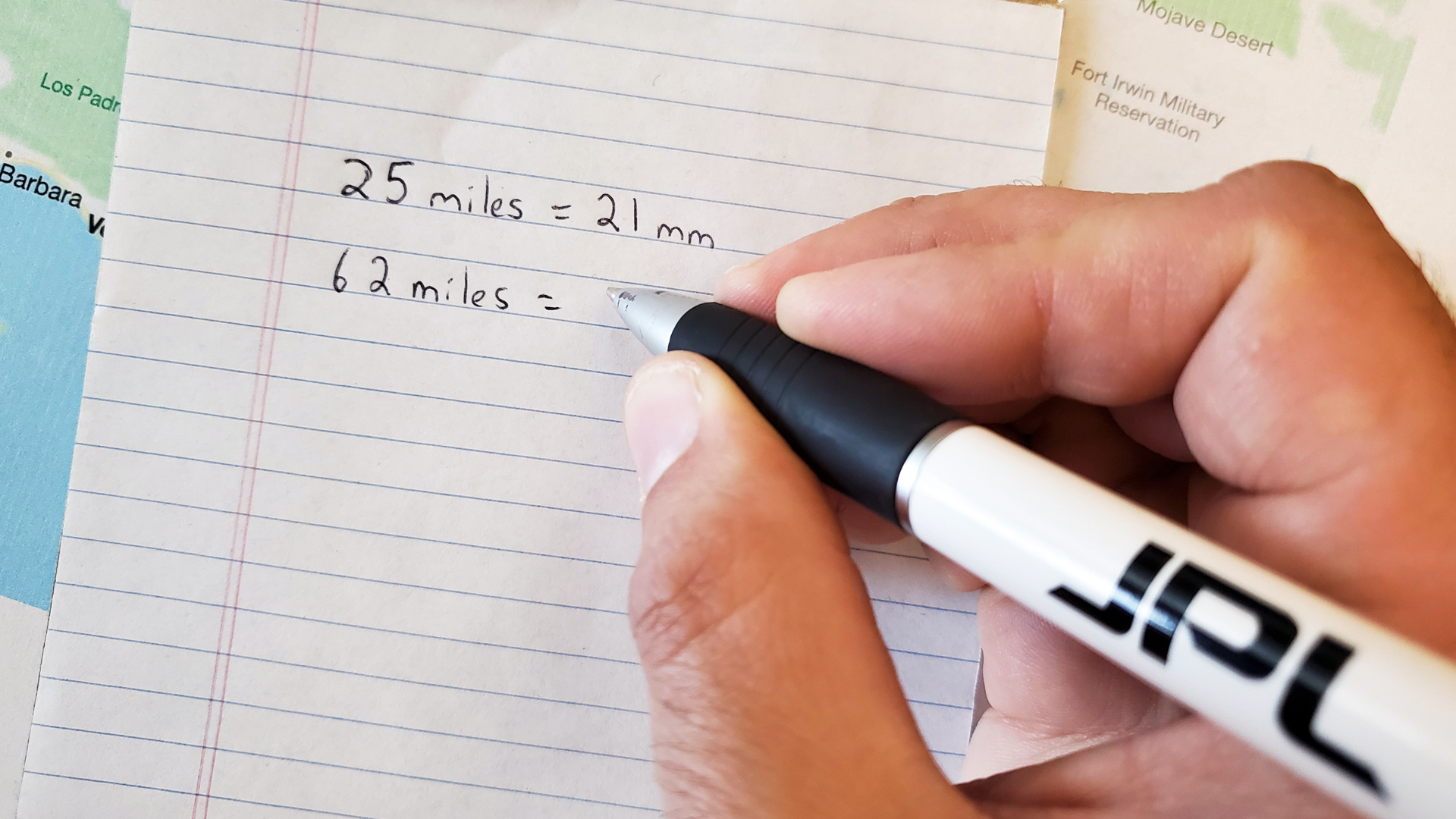 A person writes out their calculation on a piece of paper