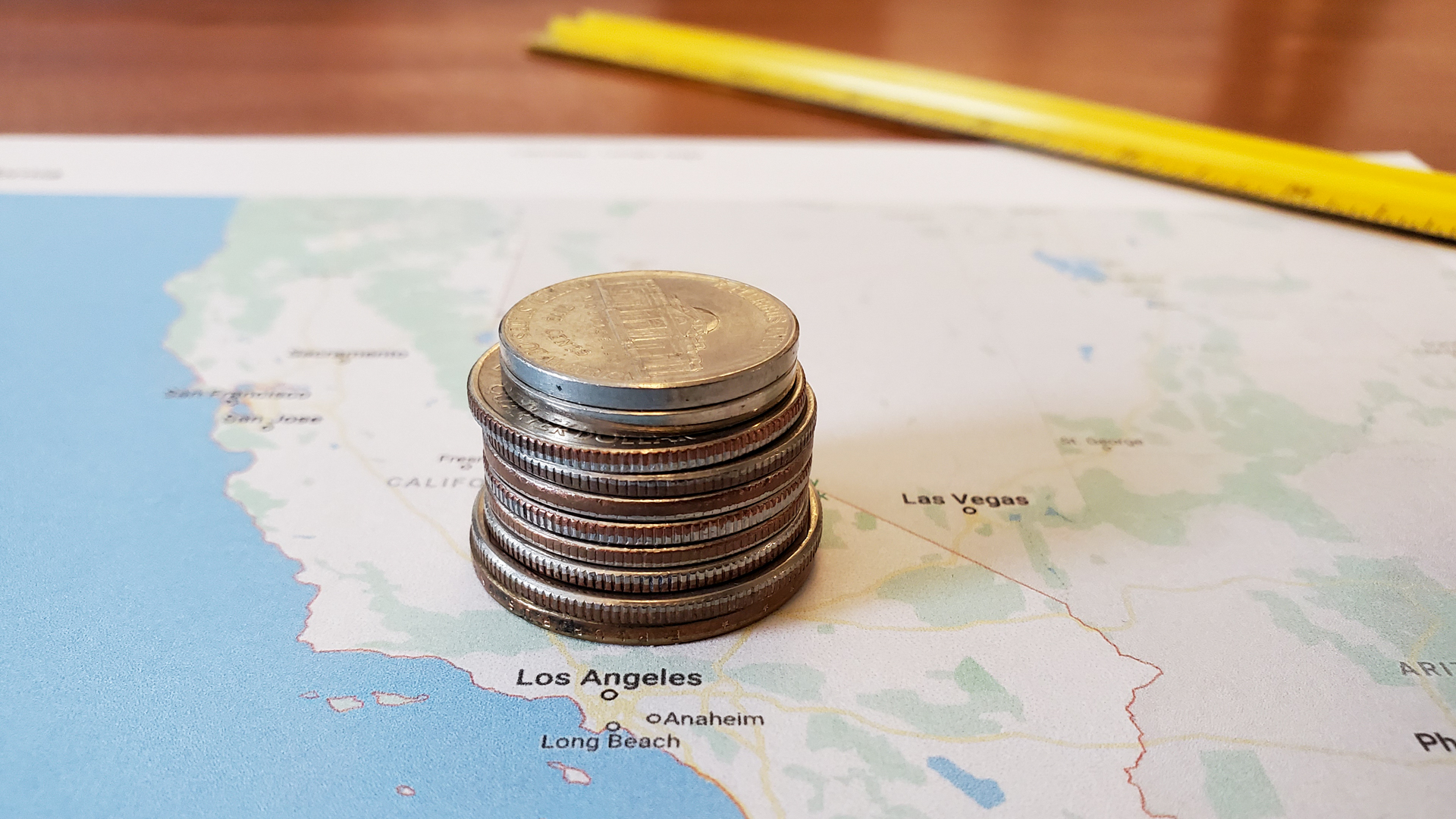 Coins stacked on top of a printed map of the Los Angeles area