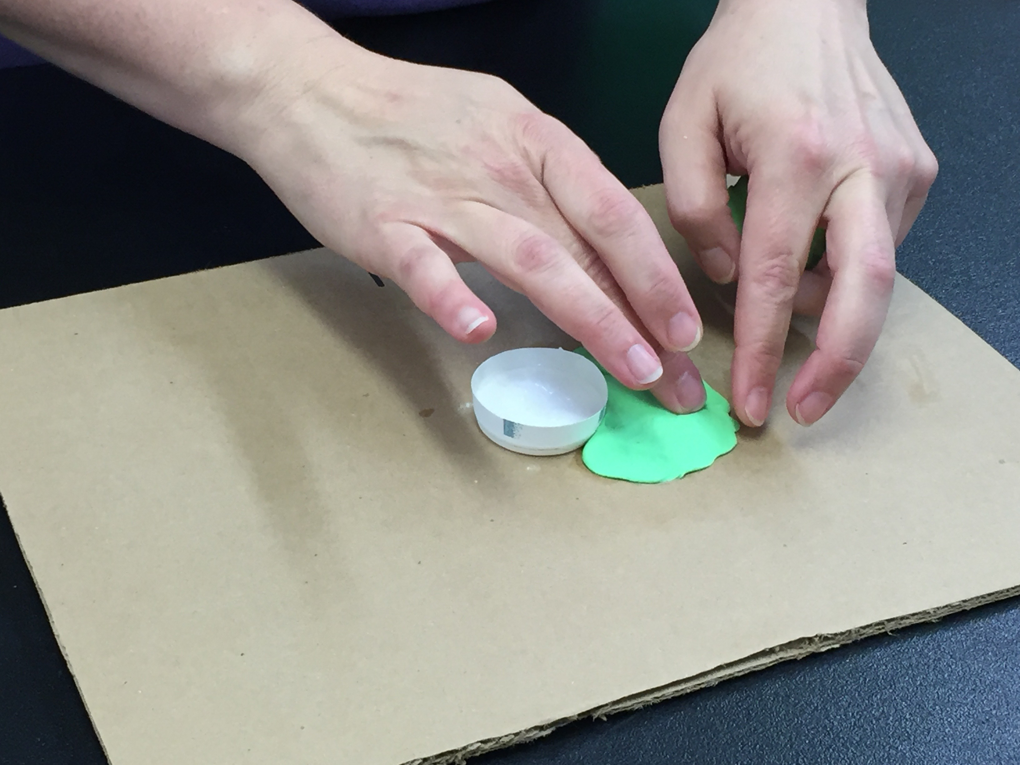 placing the play dough on the cardboard