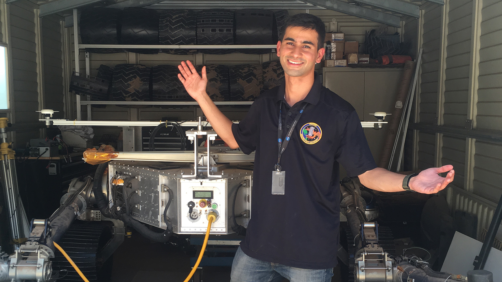 Aditya Khuller stands with his arms outstretched and poses in front of a model Mars rover in a garage at JPL.