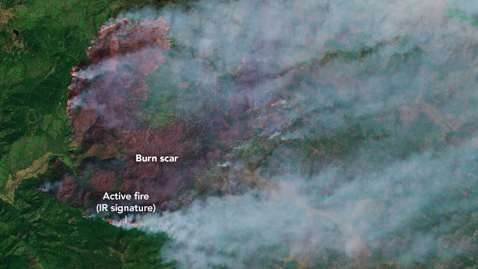A satellite image of Northern California showing a dark reddish brown section with smoke eminating from it