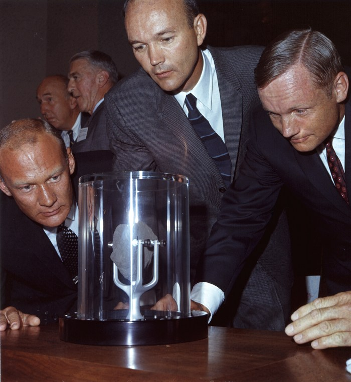 The Apollo 11 astronauts crowd around a lunar sample contained in a protective case.