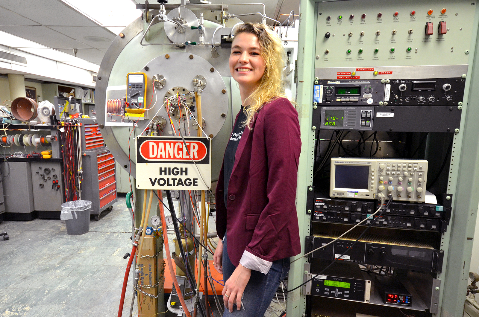 JPL intern Camille Yoke stands in front of the Danger, High Voltage sign in her lab at JPL