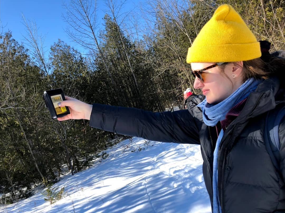 Brittney Copper stands in the snow surrounded by pine trees and holds out a device to measure the flux of solar radiation