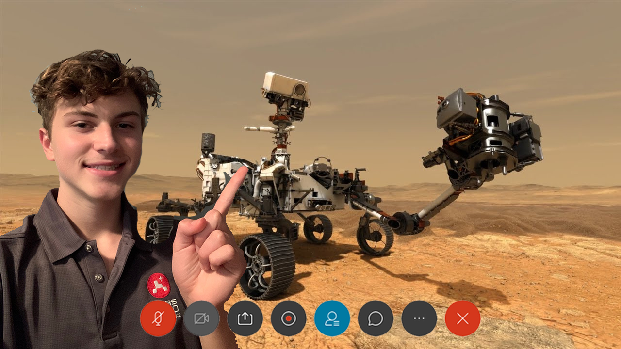 Daniel Stover is shown in a screengrab from a web meeting app pointing to an illustration of the Perseverance Mars rover.