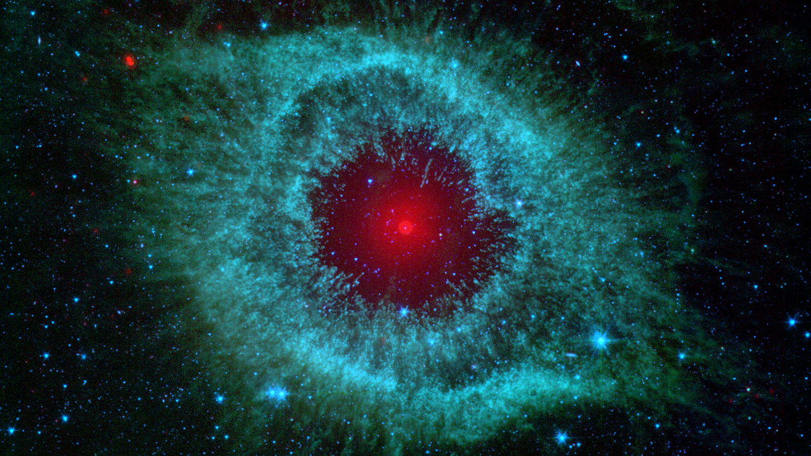 A giant red star is surrounded by an almond-shaped burst of green stellar dust, appearing like the pupil and iris of a human eye.