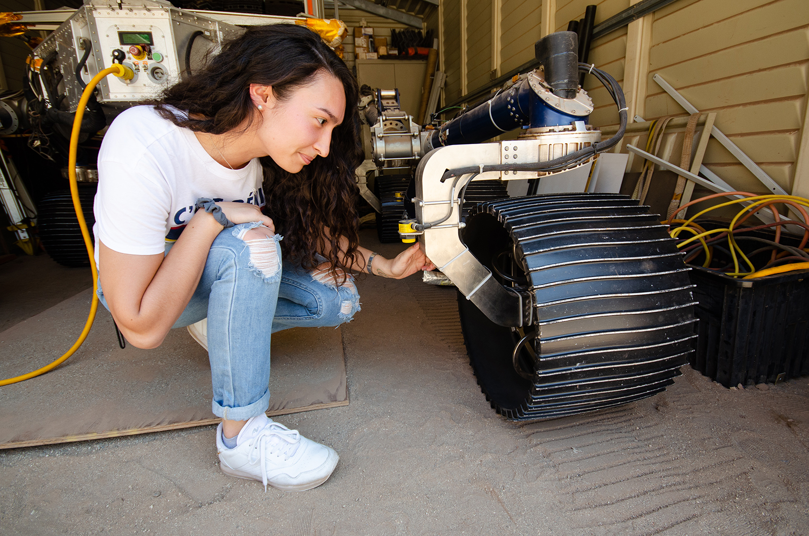 Isabel Rayas kneels down in front of the Scarecrow rover in a garage and places her hand on one of the front wheels