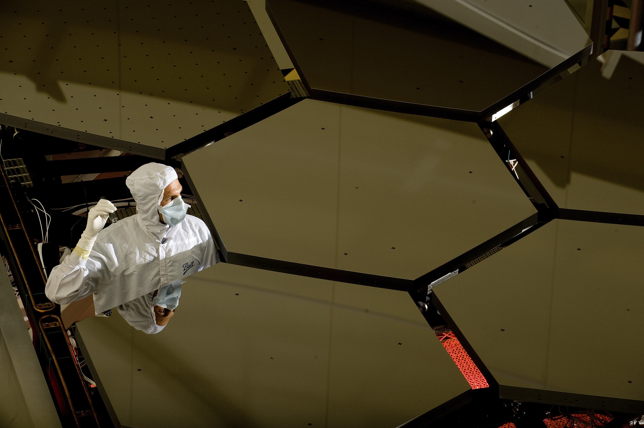 A technician in a white smock stands up in a gap between several large hexagonal mirrors forming a honeycomb shape.