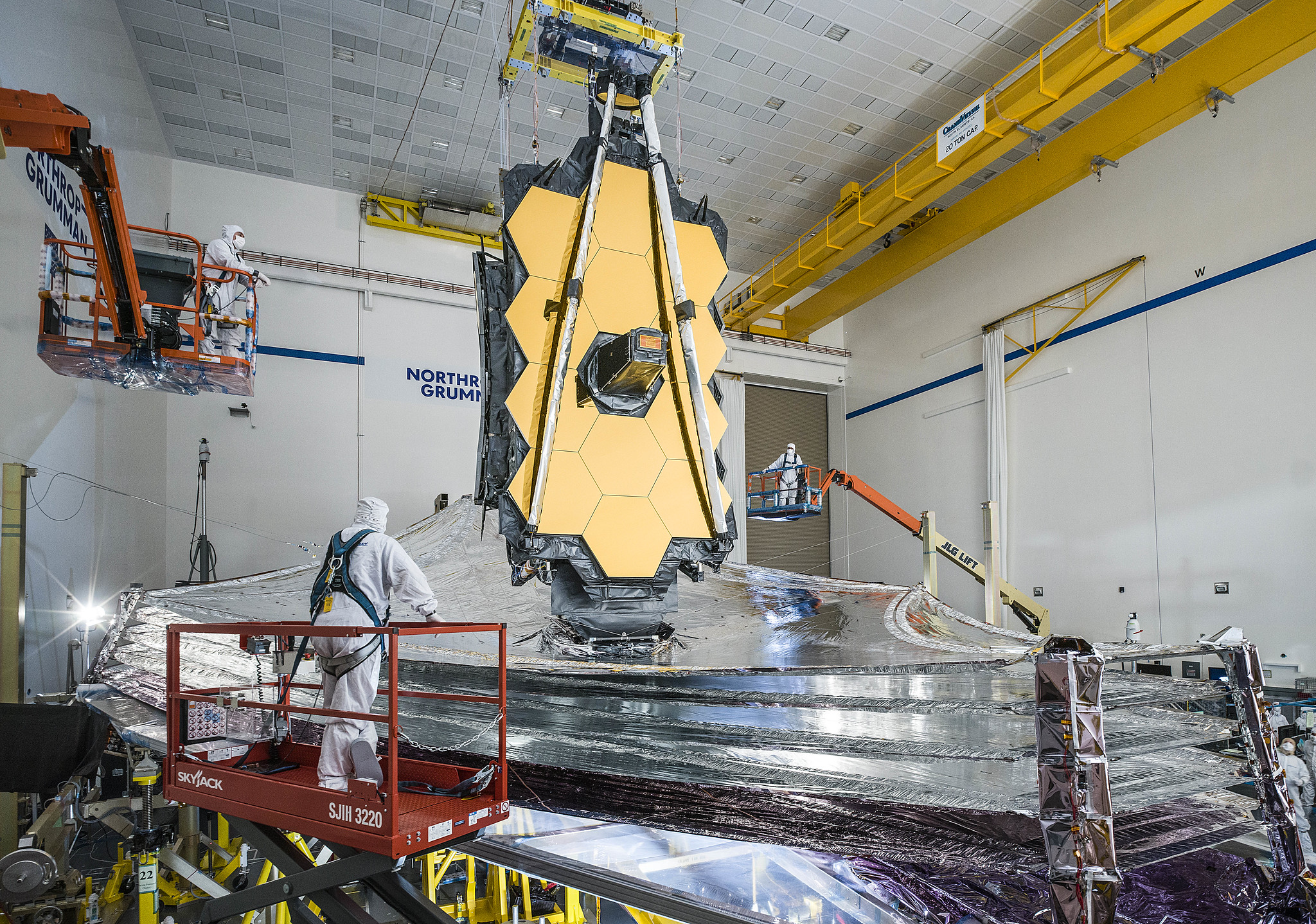 Technicians in white smocks stand on lifts looking at JWST's fully deployed sunshield in the cleanroom at Northrup Gruman. The five layers of the kite-shaped sunshield extend out around JWST's folded honeycomb-shaped mirror.