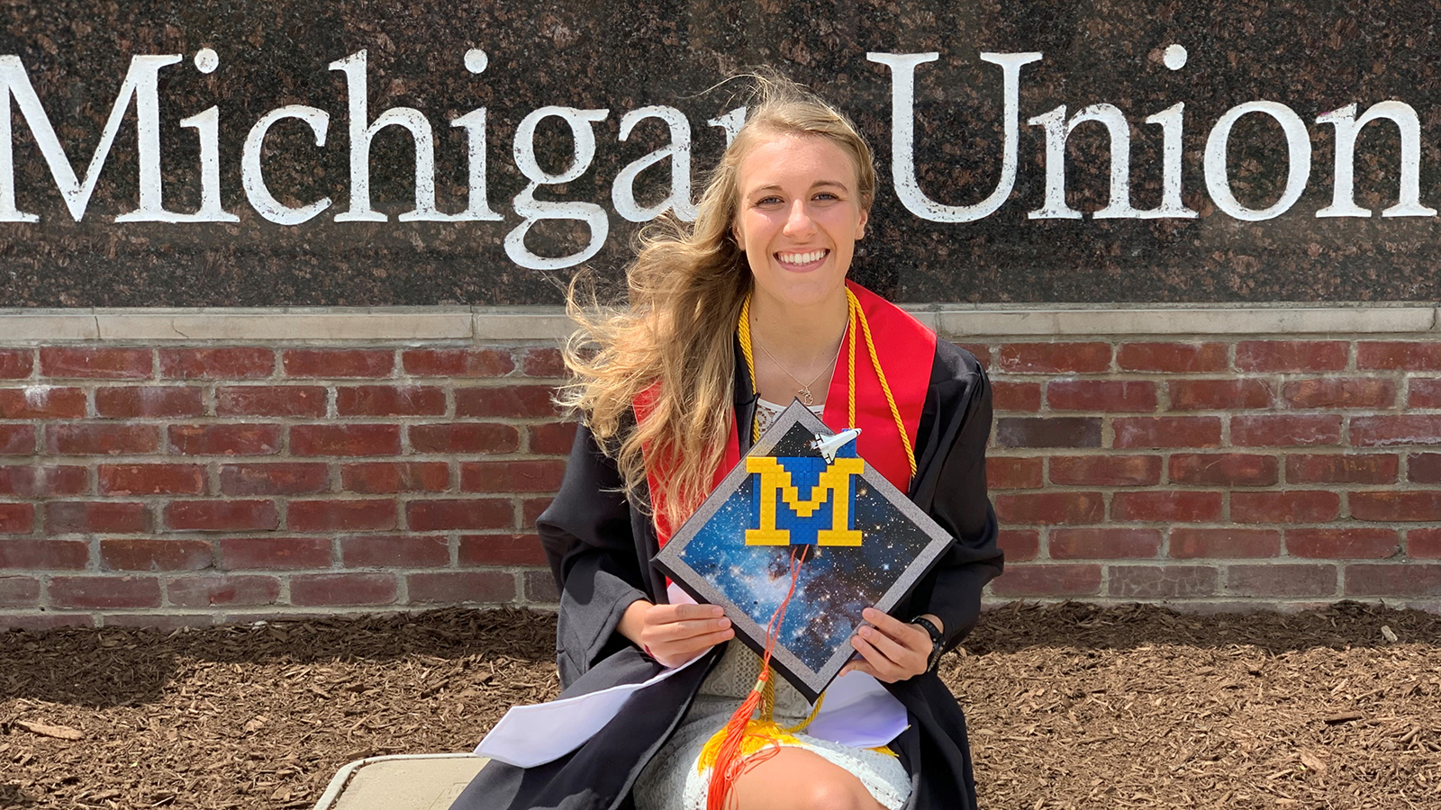 Kaelan Oldani wears her graduation gown and holds her cap while posing in front of a sign that reads 'Michigan Union.'