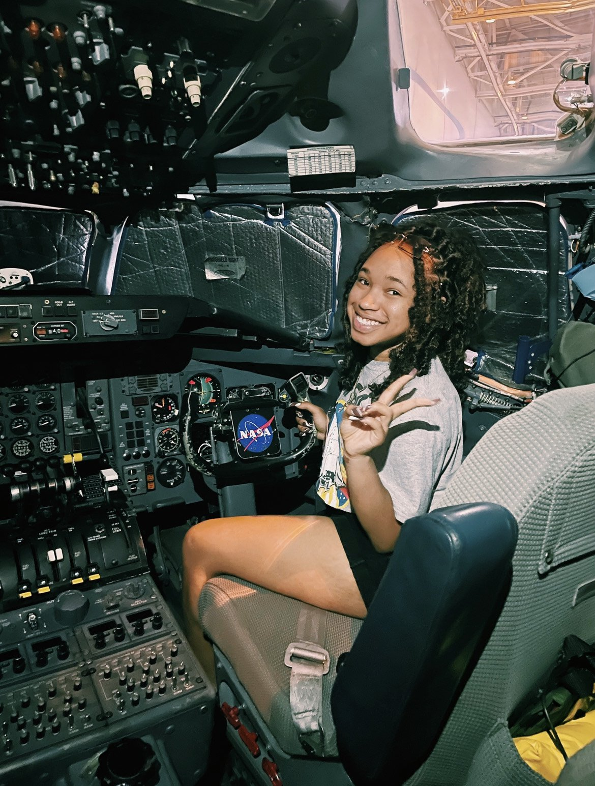 Kyndall Jones sits in the cockpit of a plane and looks back at the camera while making the peace sign with her left hand.