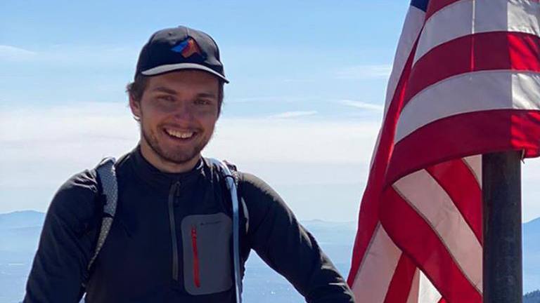 Lucas Lange wears hiking gear and poses next to an American Flag at the top of a mountain with a valley visible in the background.