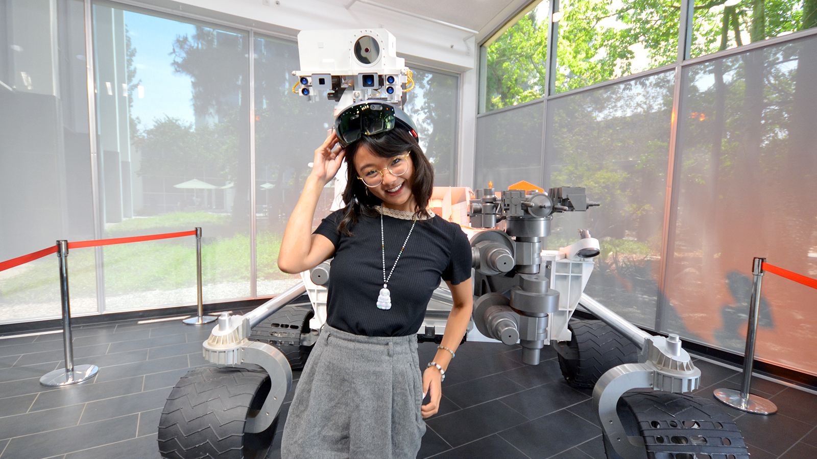 Michelle Vo poses in front of a full-size model of the Curiosity Mars rover at JPL