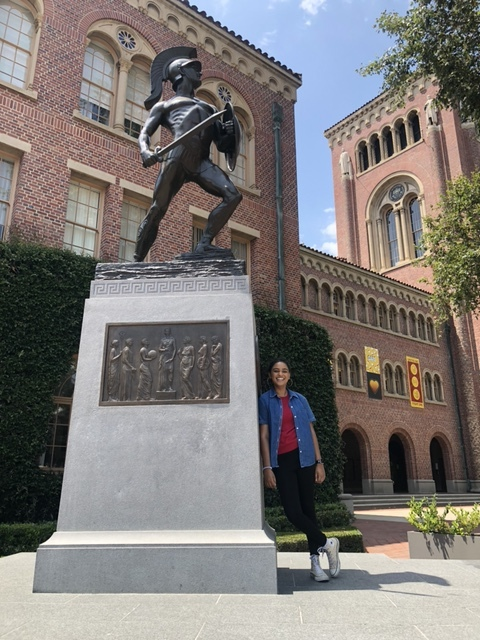 Deo leans against the base of a statue of USC's Trojan mascot.