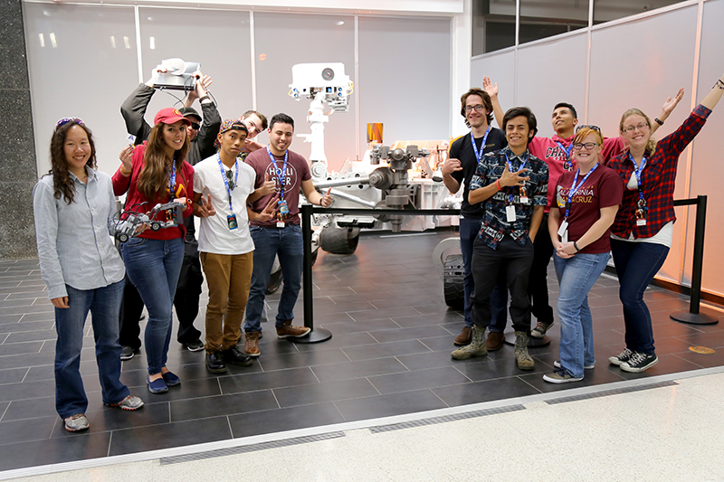 The Blue Team poses for a group photo in front of the Mars Curiosity rover model at JPL