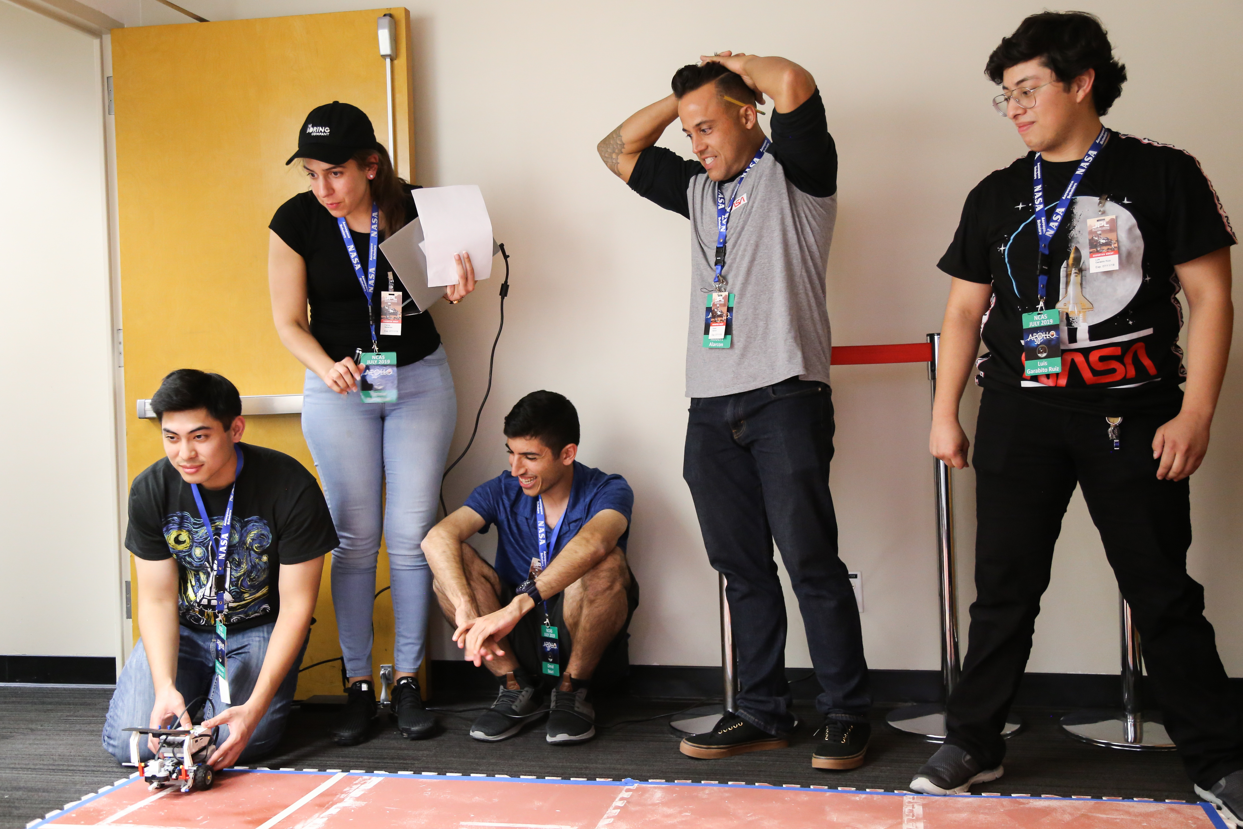 Several students stand against a wall while another sets a miniature rover on a red surface meant to simulate Martian terrain