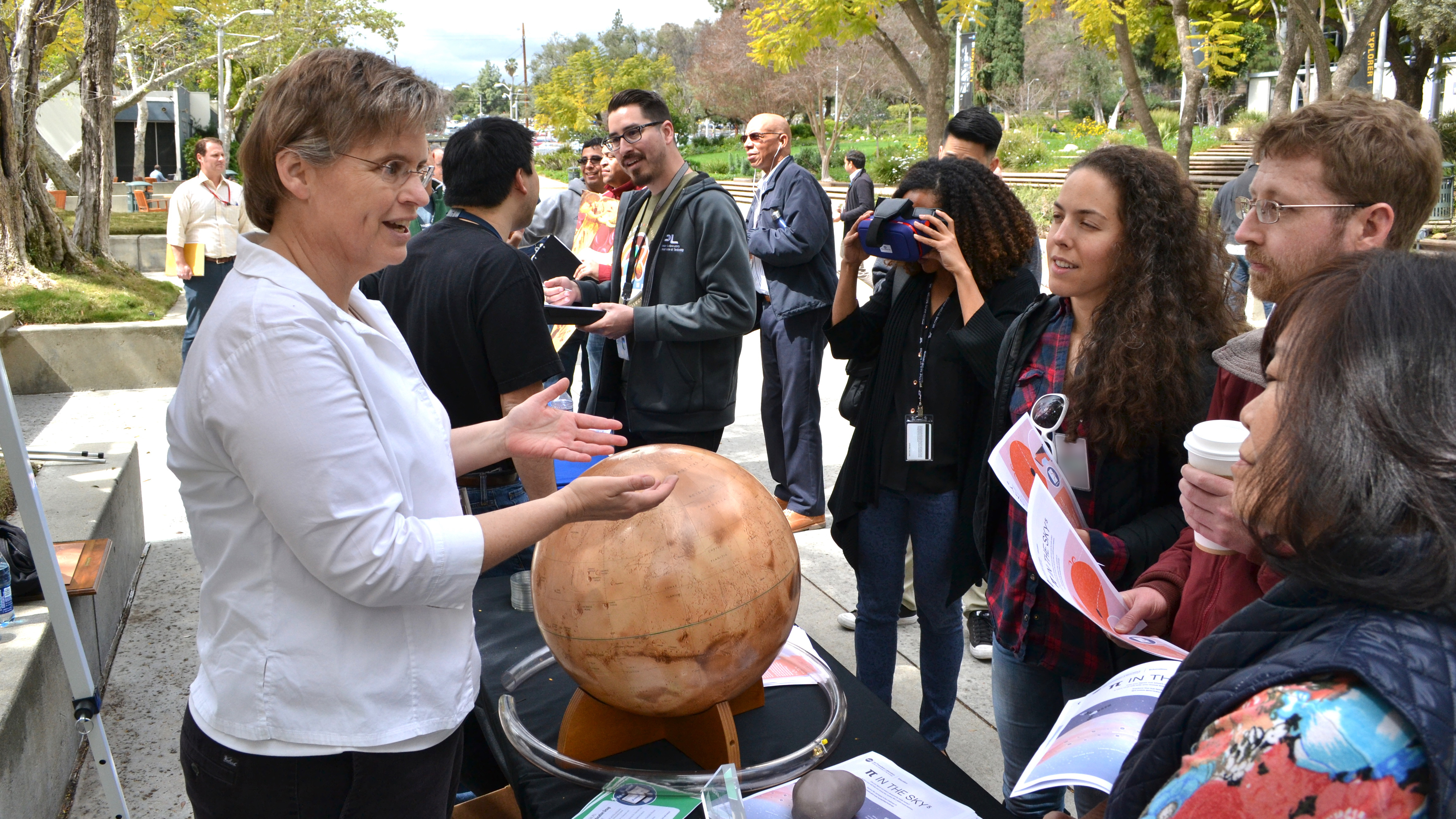 Ota Lutz stands behind a tabletop Mars globe and speaks with a group of people