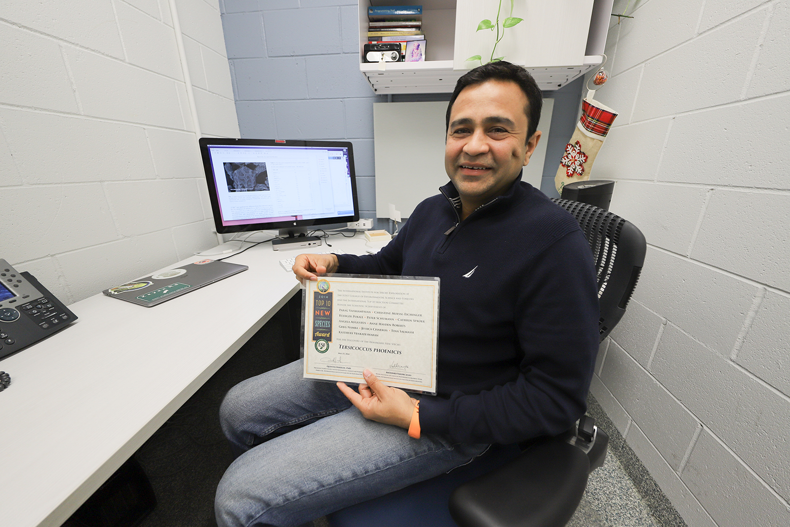 Vaishampayan sits in his stark white office holding a laminated award.