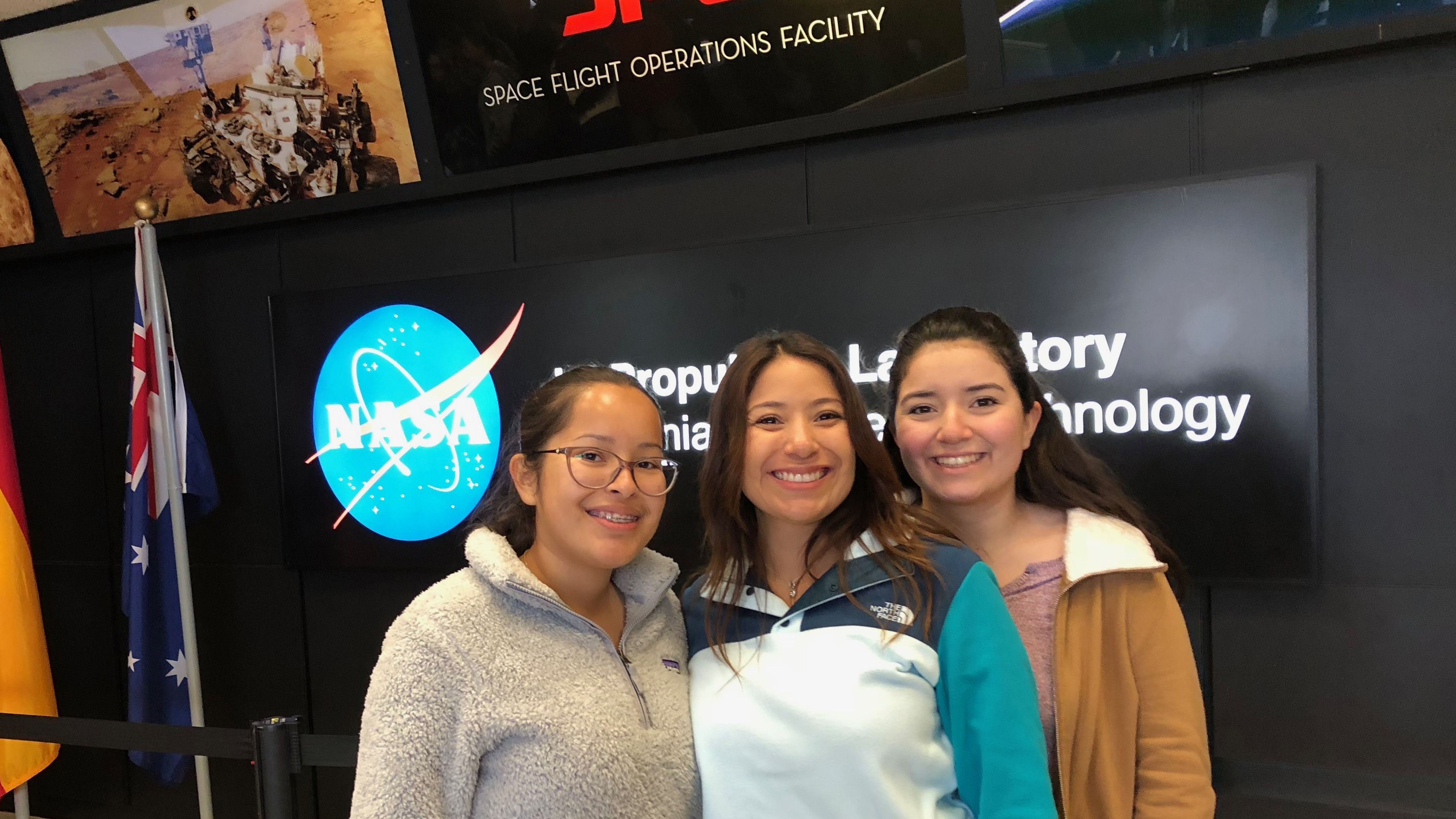 Rebecca and her mom and sister pose for a photo in the lobby of JPL's mission control with NASA/JPL logo behind them.