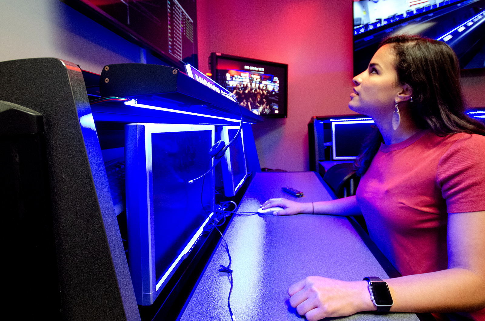 Santini De Leon sits in the Space Flight Operations center at JPL in a room with red and blue lighting and looks up at a screen showing live spacecraft communications.