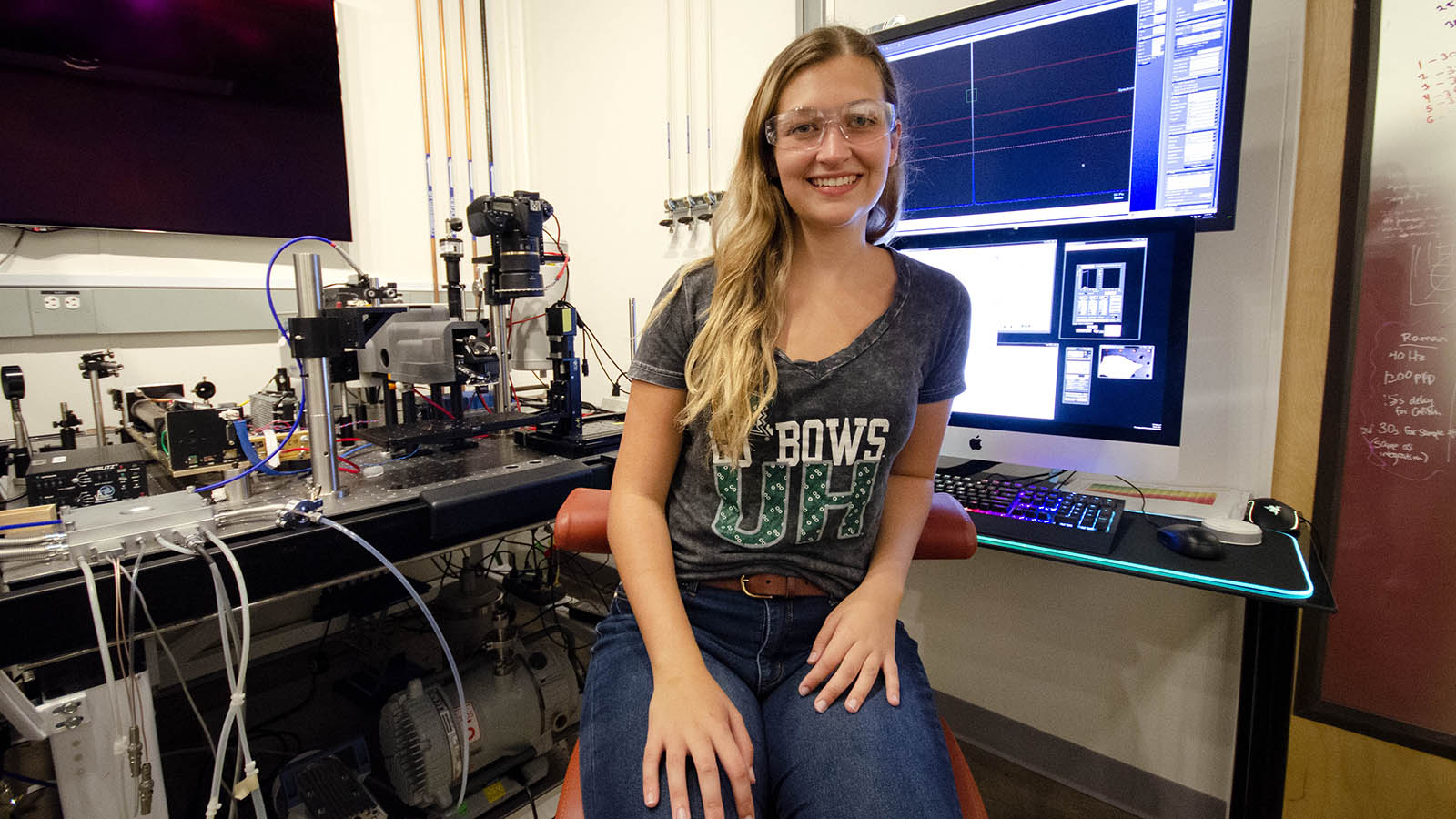 Ireland wears lab goggles and a University of Hawaii T-shirt. She sits in front of several screens and the lab version of SHERLOC.