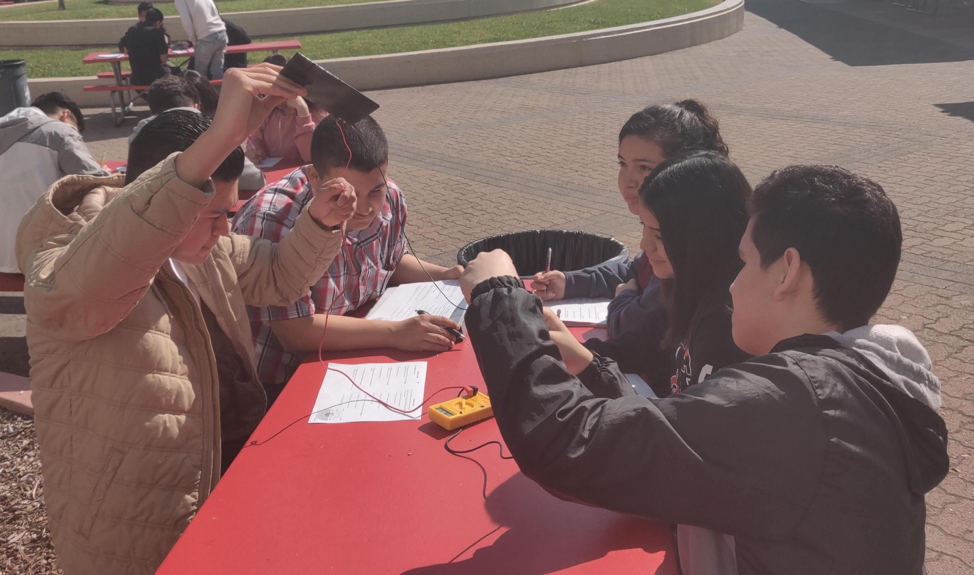 Students sit around a red table, one holding a solar panel in the air with wires attached to a small device. Other students examine the data on the device and write the results.