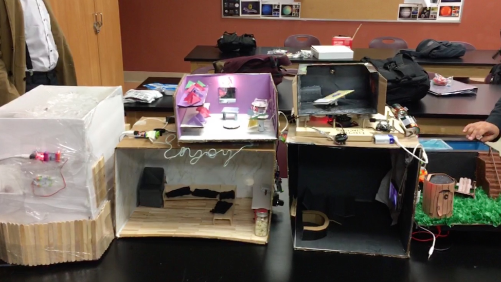 Small cardboard boxes with dioramas of living rooms, an outdoor scene and a bedroom sit side-by-side on a large black desk.