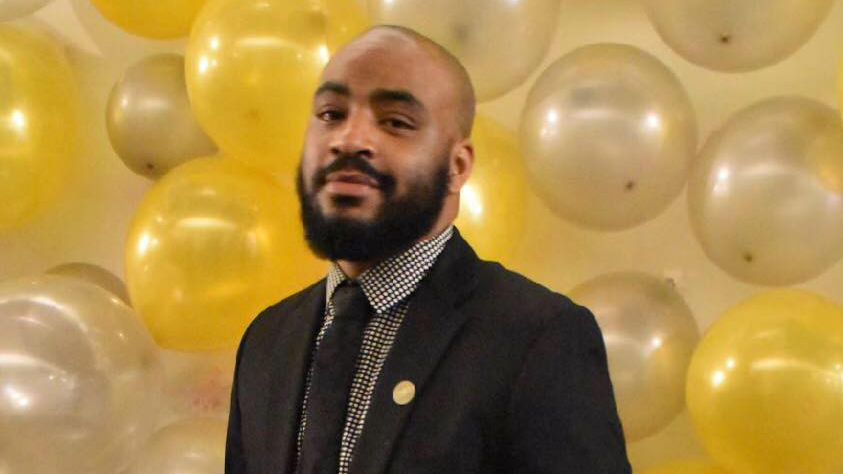 Yohn Ellis, wearing a suit and tie, poses in front of yellow and gold balloons.