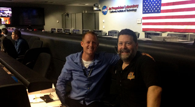 Andrew Crawford sits with Todd Barber in JPL's Mission Control