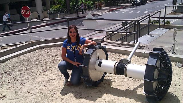 JPL Intern Lorenia Jimenez Miramontes inspects a quadrotor at JPL