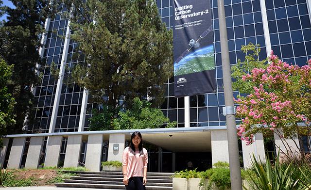 JPL Intern Yanbing Zhu in front of an OCO-2 banner at JPL
