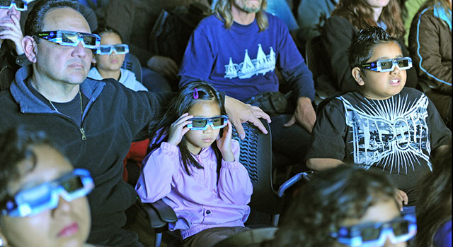 An audience wears 3-D glasses while in a darkened theater