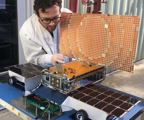 JPL engineer Joel Steinkraus works with one of the MarCO CubeSats during an outdoor test of its solar arrays.