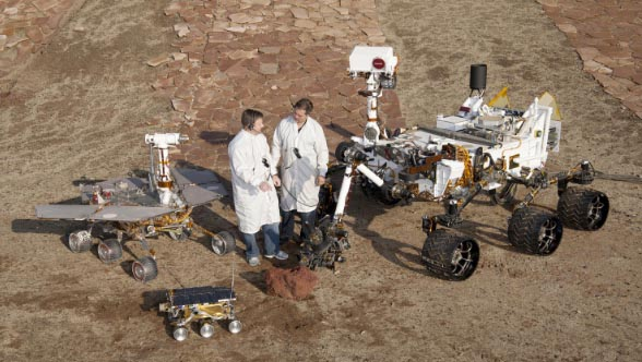 Past and present mars rover models displayed next to two scientists