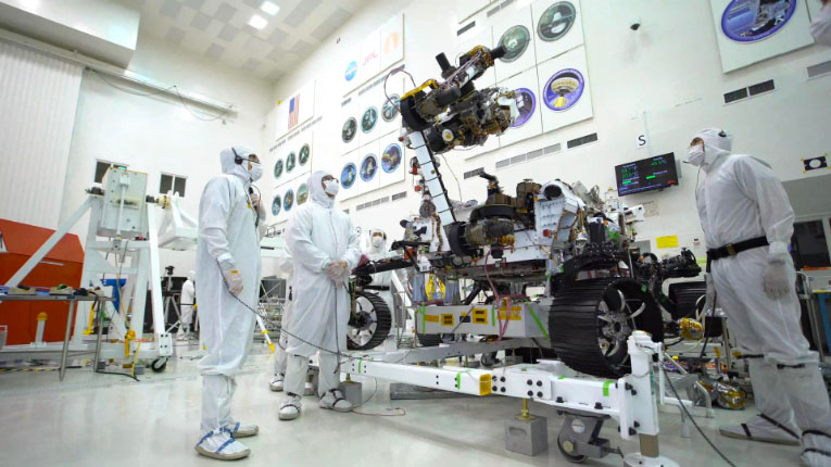 Engineers in clean suits working on the rover