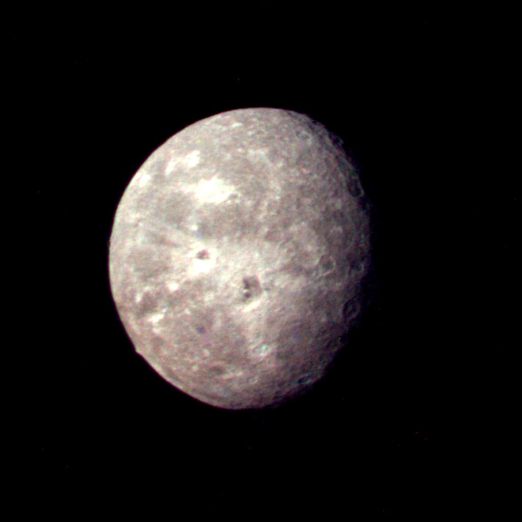 This image of Oberon, Uranus' outermost moon, was captured by NASA's Voyager 2 on Jan. 24, 1986. Clearly visible are several large impact craters in Oberon's icy surface surrounded by bright rays.
