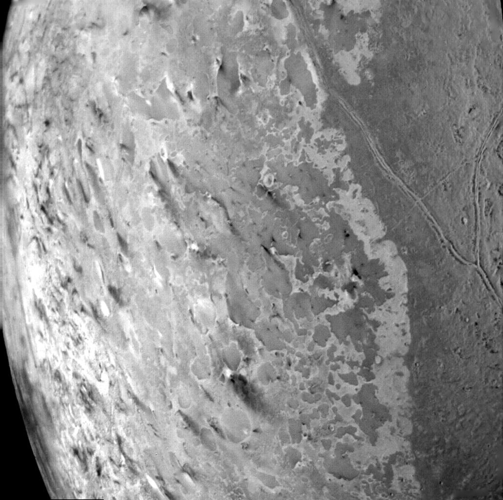 This image from NASA's Voyager 2 of the south polar terrain of Triton, was taken on Aug. 25, 1989 revealing about 50 dark plumes or 'wind streaks' on the icy surface. The plumes originate at very dark spots generally a few miles in diameter and some are m