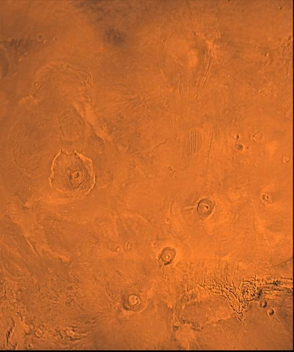 The Tharsis region of Mars; north toward top. This scene shows the Tharsis bulge, a huge ridge covered by the 3 large aligned Tharsis Montes shield volcanoes (from lower l to r): Arsia, Pavonis, and Ascraeus Mons as seen by NASA's Viking spacecraft.