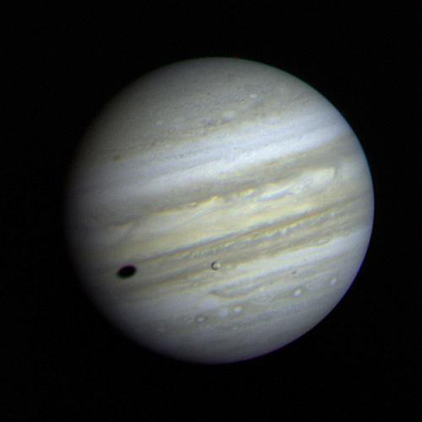 Jupiter's satellite Io poses before the giant planet in this photo returned January 17, 1979. The satellite's shadow can be seen falling on the face of Jupiter at left. Io is traveling from left to right in its orbit around Jupiter.
