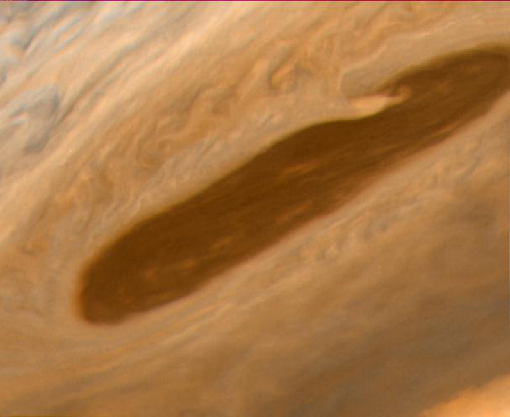 This image returned NASA's Voyager 2 shows one of the long dark clouds observed in the North Equatorial Belt of Jupiter. A high, white cloud is seen moving over the darker cloud, providing an indication of the structure of the cloud layers.