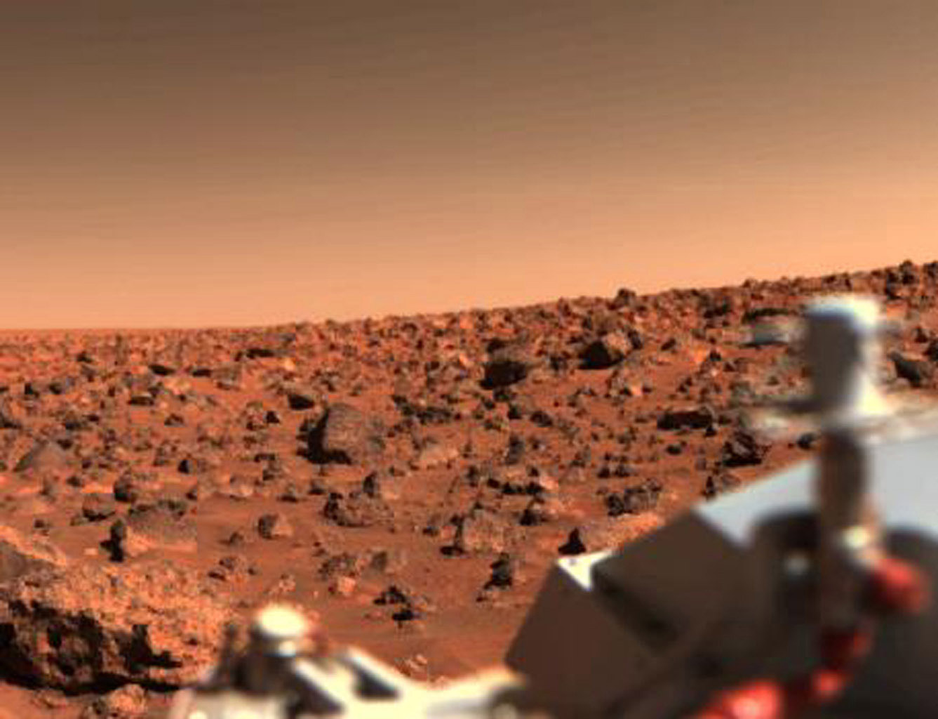 Looking south from NASA's Viking 2 on Sept. 6, 1997, the orange-red surface of the nearly level plain upon which the spacecraft sits is seen strewn with rocks as large as three feet across.