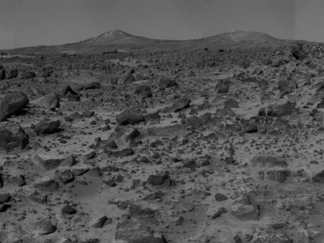 The two hills in the distance, approximately one to two kilometers away, have been dubbed the 'Twin Peaks.' The image was taken by NASA's Imager for Mars Pathfinder (IMP) after its deployment on July 7, 1997.