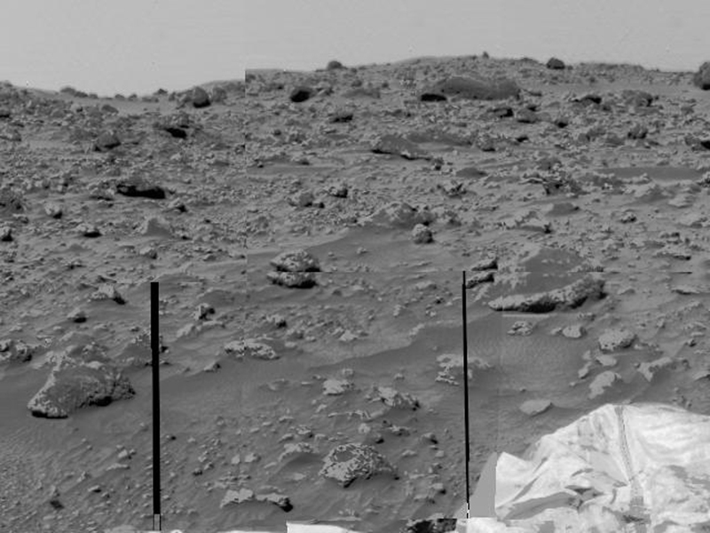 An area of very rocky terrain at the Ares Vallis landing site, along with the lander's deflated airbags, were imaged by NASA's Imager for Mars Pathfinder (IMP). The two dark lines are missing data.