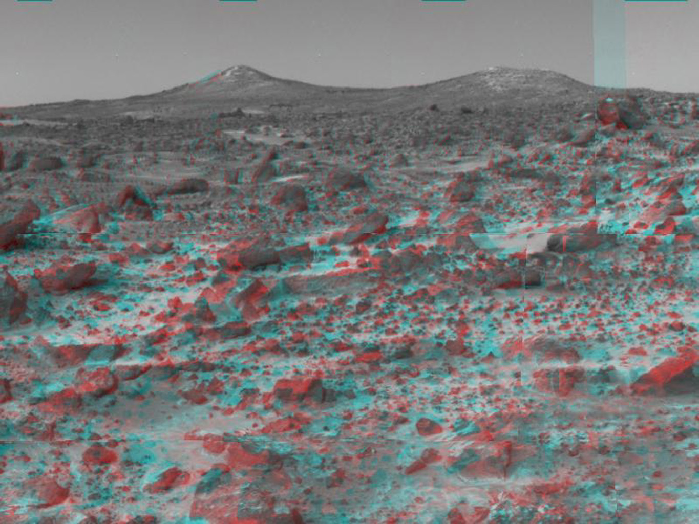 The two hills in the distance in this stereo image from NASA's Mars Pathfinder have been dubbed the 'Twin Peaks.' 3-D glasses are necessary to identify surface detail.